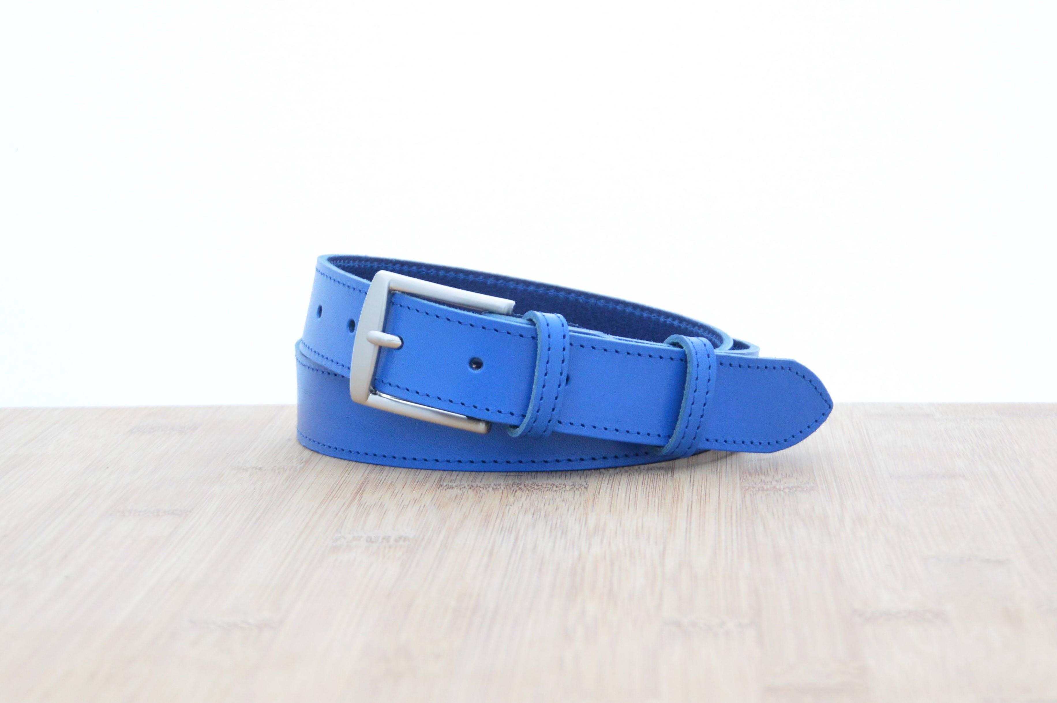 ceinture en cuir bleu avec surpiqûre posé sur du bois 1f60d8b325a