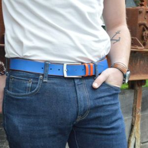 ceinture en cuir bicolore orange et bleu porté sur un jean brut devant une poutre rouillée