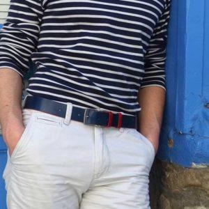 ceinture en cuir bicolore bleu et rouge porté sur un short blanc