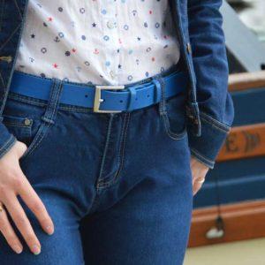 ceinture en cuir bleu porté sur un jean devant un bateau