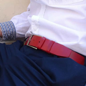 ceinture en cuir rouge porté sur un pantalon de costume bleu marine