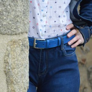ceinture en cuir bleu porté sur un jean derrière un mur
