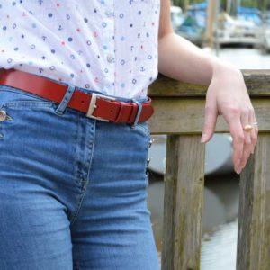 ceinture en cuir rouge porté sur un jean devant des bateaux