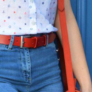 ceinture en cuir rouge porté sur un jean devant une porte bleu