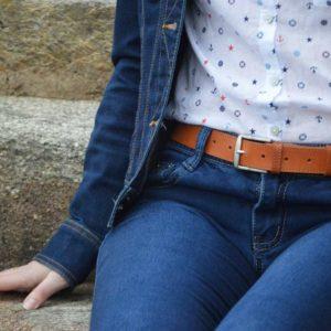 ceinture en cuir marron surpiquée porté sur un jean assis sur de la pierre