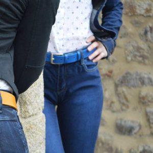 ceinture en cuir jaune surpiquée derrière un mur et ceinture en cuir bleu devant un mur