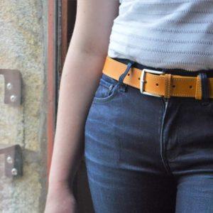 ceinture en cuir jaune surpiquée porter sur un jean bleu foncé devant une fenêtre