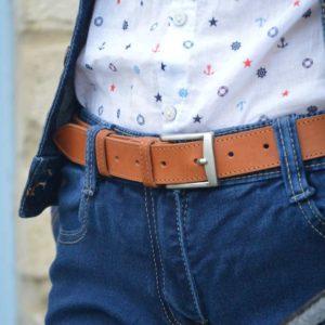 ceinture en cuir marron surpiquée porté sur un jean bleu foncé