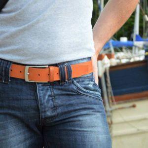 ceinture en cuir marron surpiquée porté sur un jean devant un bateau