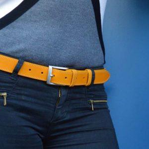ceinture en cuir jaune surpiquée porter sur un jean bleu foncé