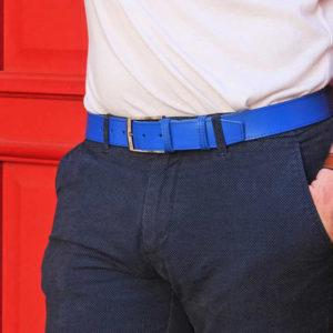 ceinture en cuir bleu surpiquée porté sur un chino bleu marine devant une porte rouge