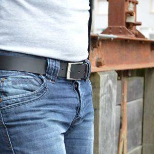 ceinture en cuir noir porté sur un jean devant une poutre rouillé