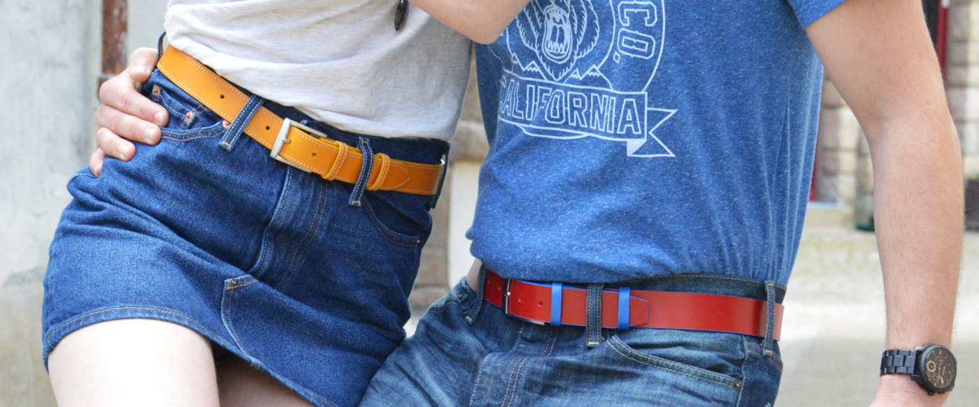 couple qui se tient par la taille avec un ceinture en cuir bicolore rouge et bleu et une ceinture jaune surpiquée portées sur du jean
